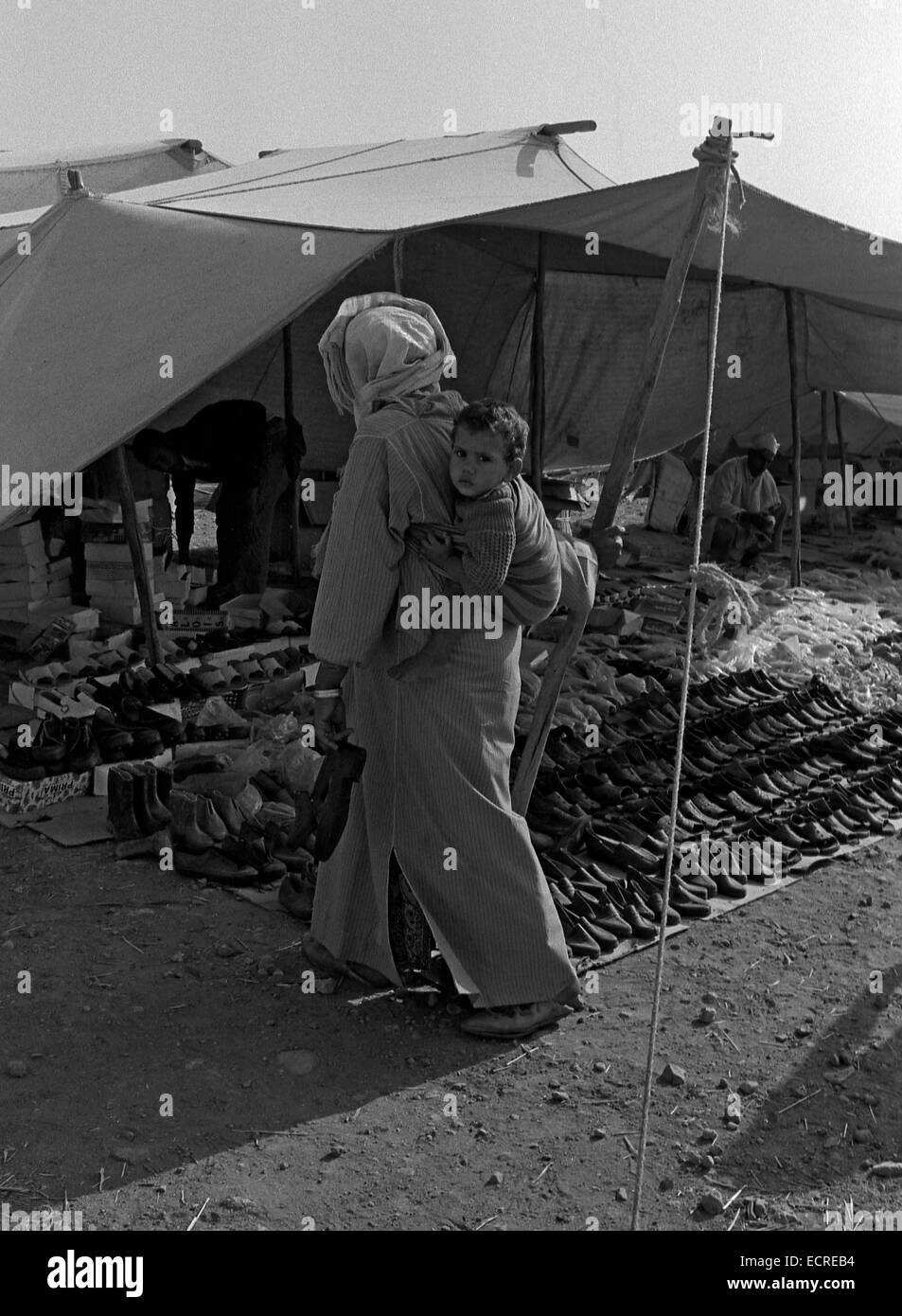MIDDLE ATLAS, MOROCCO - JULY 1979: A woman carries her child on her back, after having bought shoes in a Berber - Stock Image
