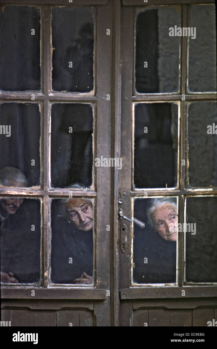 Three old women seen through the window of his house, what happens on the street of a Castilian village on May, - Stock Image
