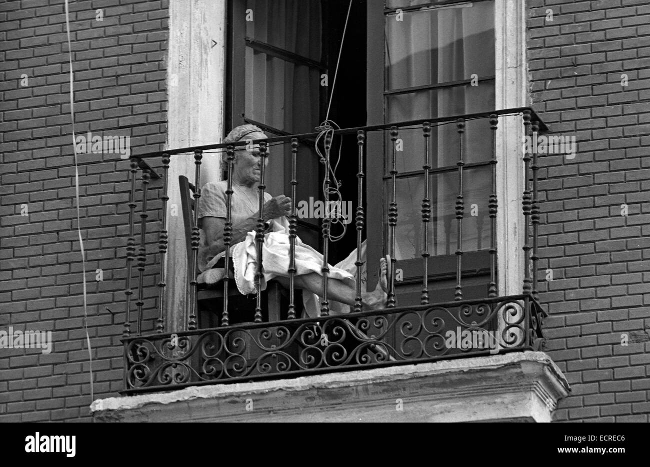 An Elderly Woman Sewing On The Balcony Of His House To Avoid Heat On July,  1979 In Valladolid, Spain