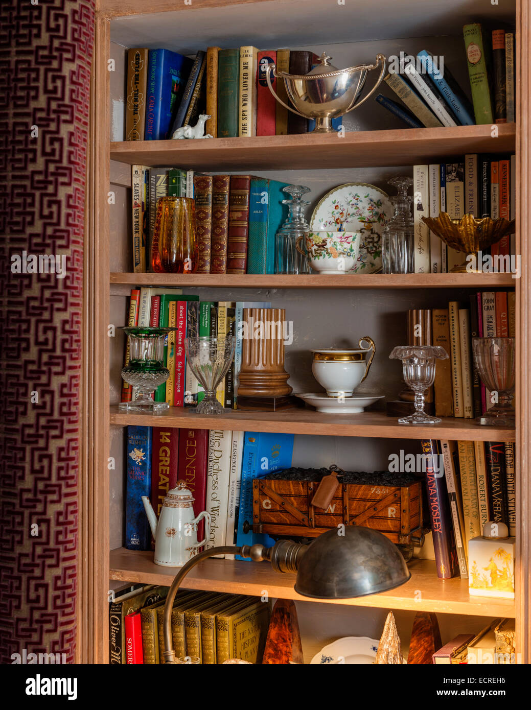 Assorted books, glassware and silverware on open wooden shelving - Stock Image