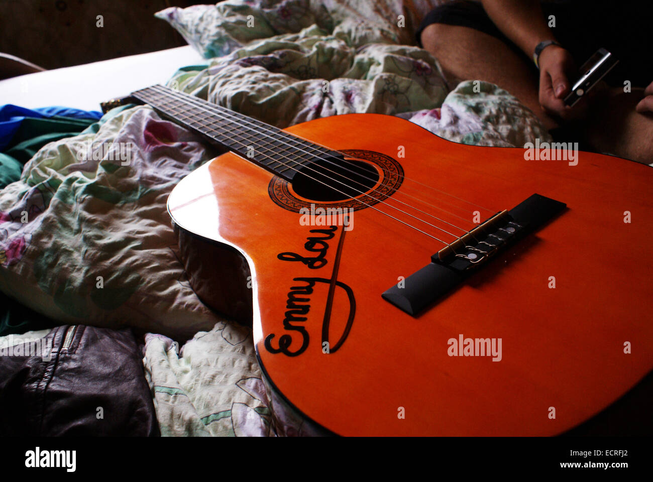 An Acoustic Guitar With The Name Emmy Lou Inscribed Sits On A Bed