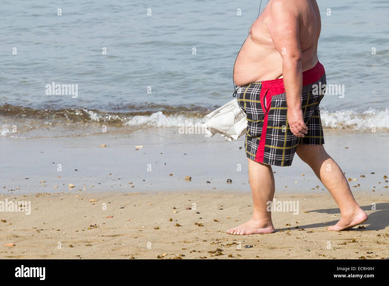 obese-man-walking-on-beach-ECRHXH.jpg