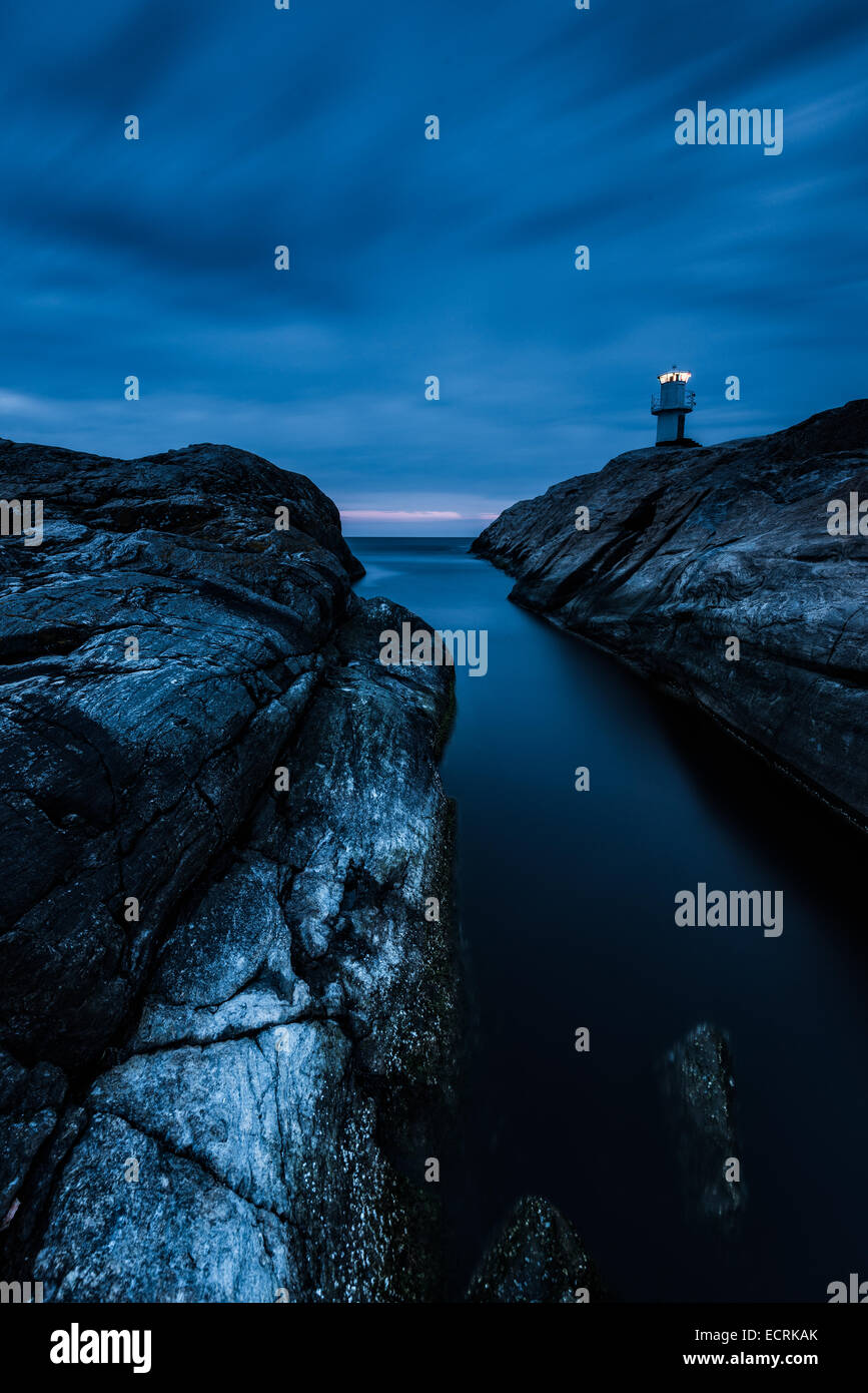 Lighthouse and a rocky shore at night - Stock Image