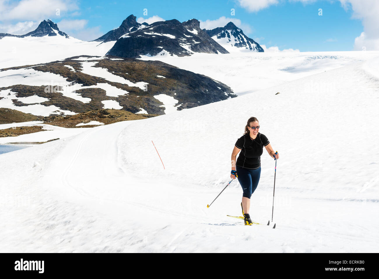 Woman in summer clothes skiing at the top of a mountain - Stock Image