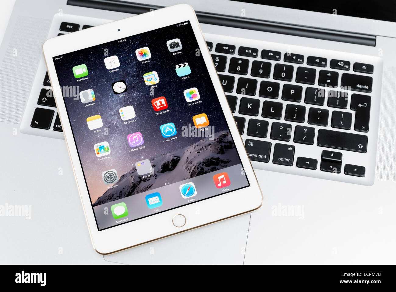 Apple iPad Mini 3 tablet on MacBook laptop computer - Stock Image