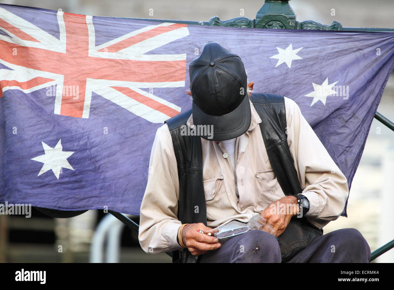 An elderly busker with leather cap and vest taking a cigarette break at Circular Quay, Sydney, NSW, Australia. - Stock Image