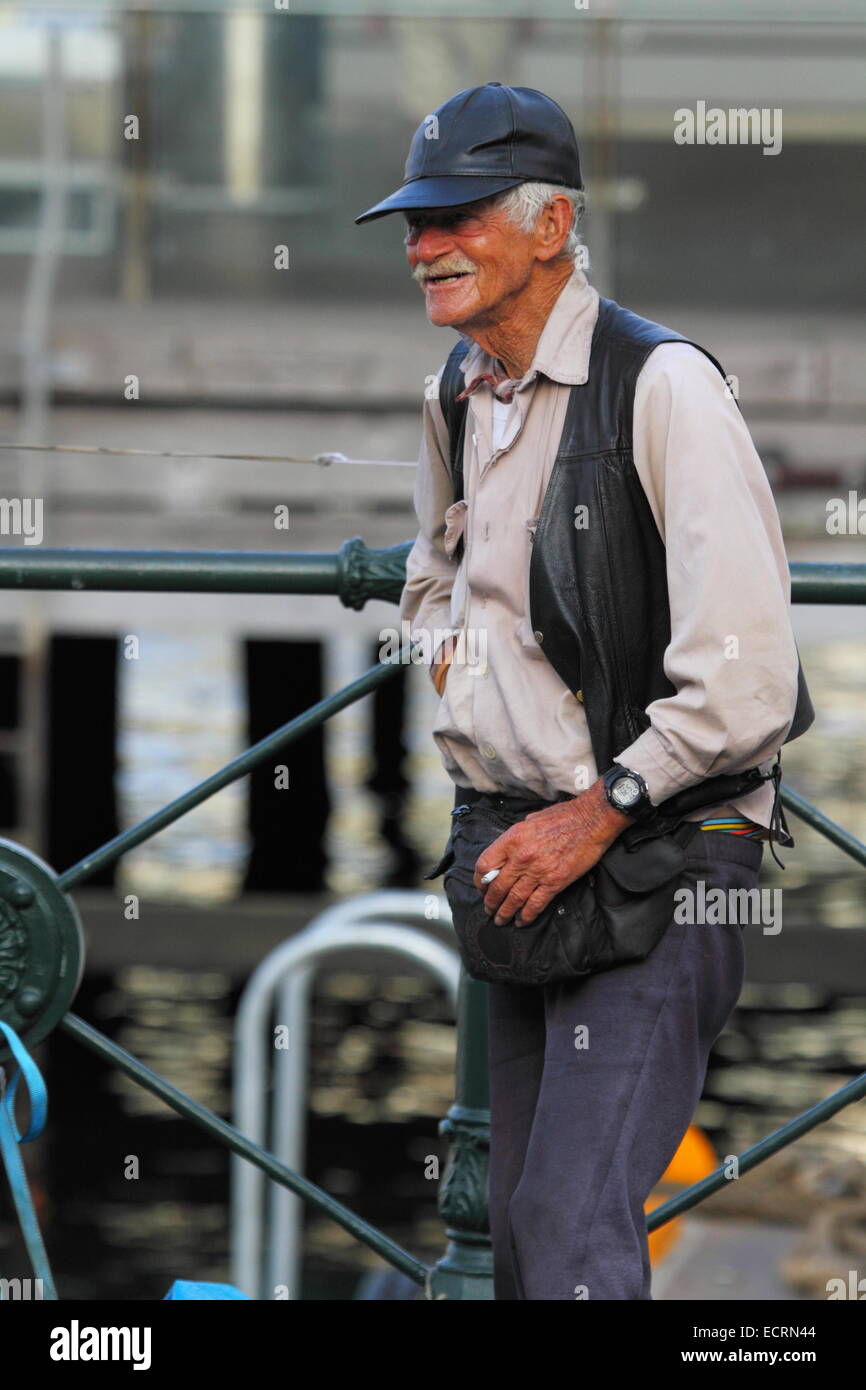 An elderly busker with leather cap and vest takes a smoke-break at Circular Quay, Sydney, NSW, Australia. - Stock Image