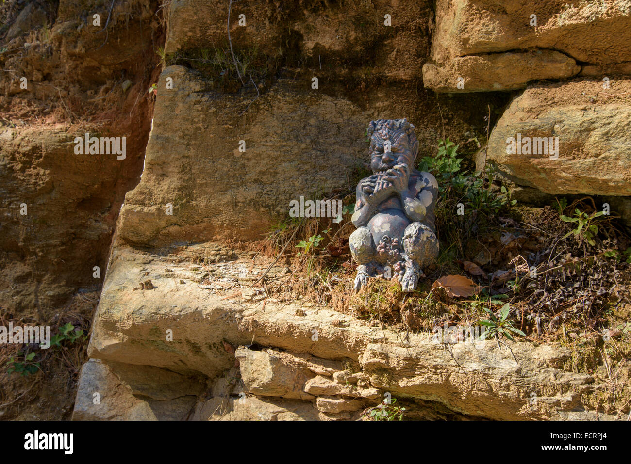 Garden statue of Pan playing flute sitting on rock ledge - Stock Image