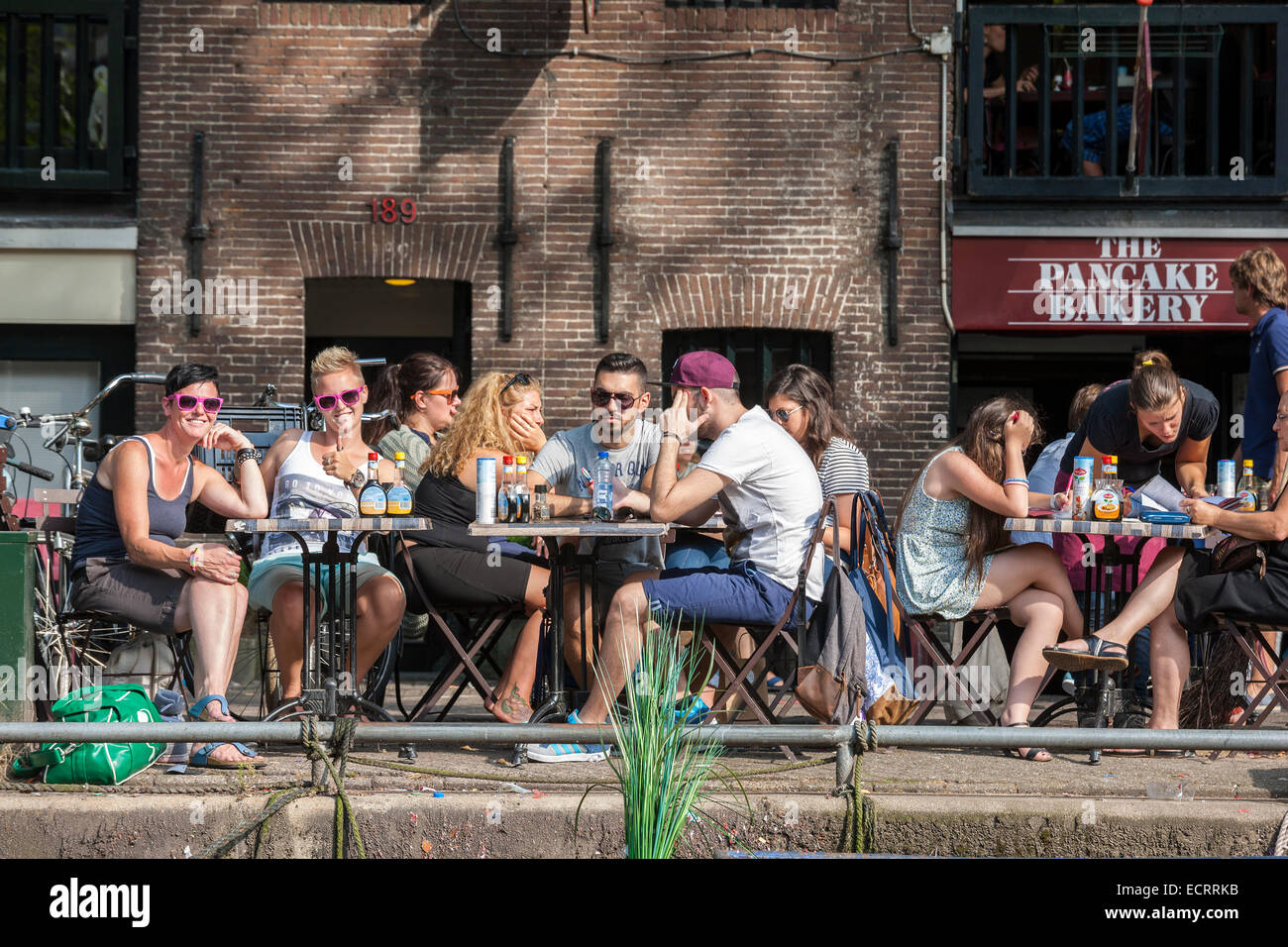 Amsterdam Pancake Bakery Restaurant on the Prinsengracht canal. People sitting on the edge of the water. Seen from - Stock Image