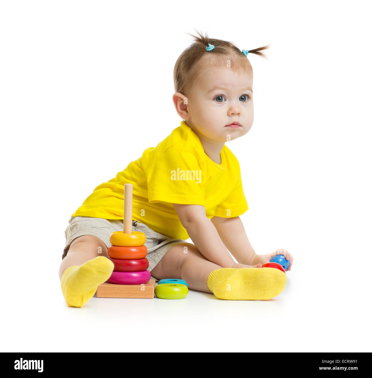baby girl playing with colorful pyramid isolated on white - Stock Image