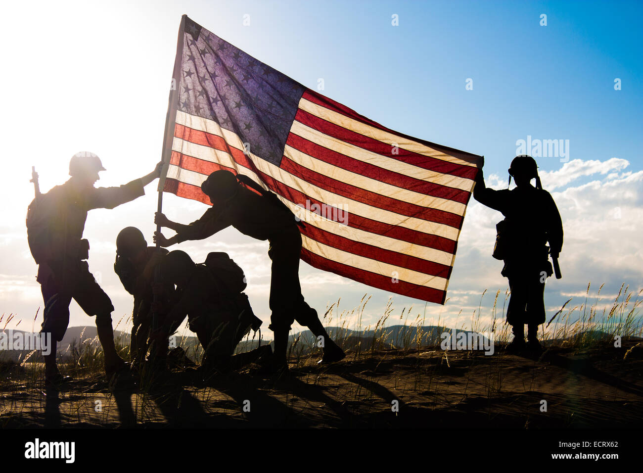 Soldiers in WWII uniforms recreating the raising of the flag - Stock Image