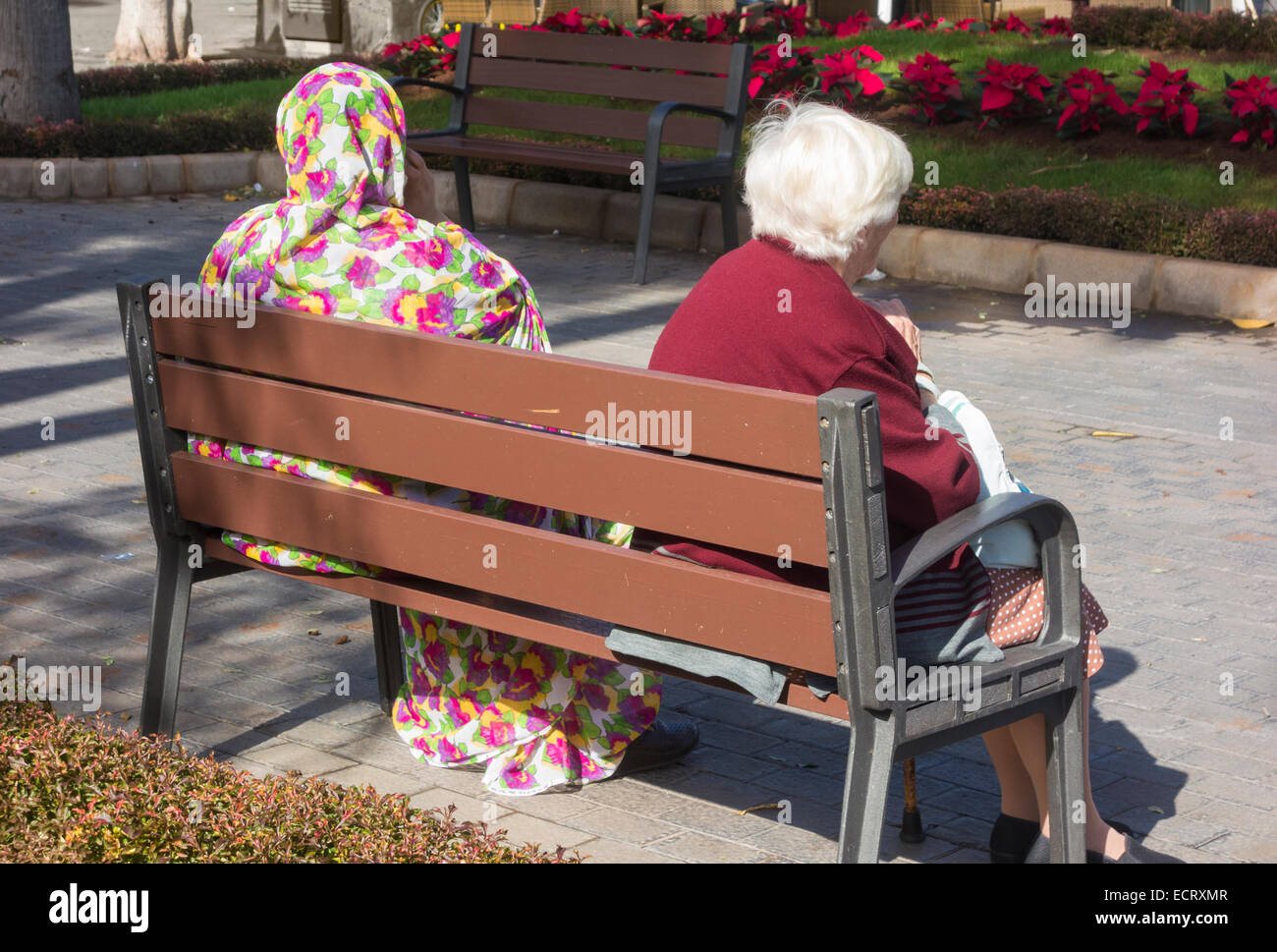 Elderly Spanish woman and woman from Western Sahara sitting on seat in Las Palmas, Gran Canaria, Canary Islands, - Stock Image