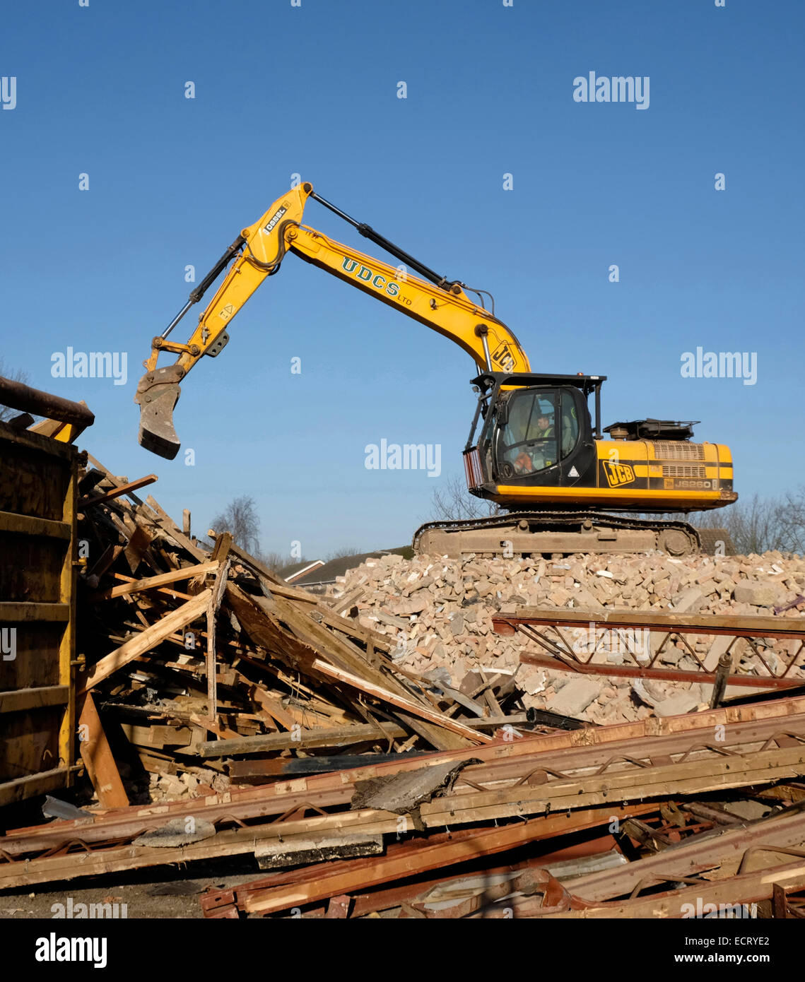 Heavy plant machinery removing rubble from a demolished house, Grantham, Lincolnshire, England, UK - Stock Image