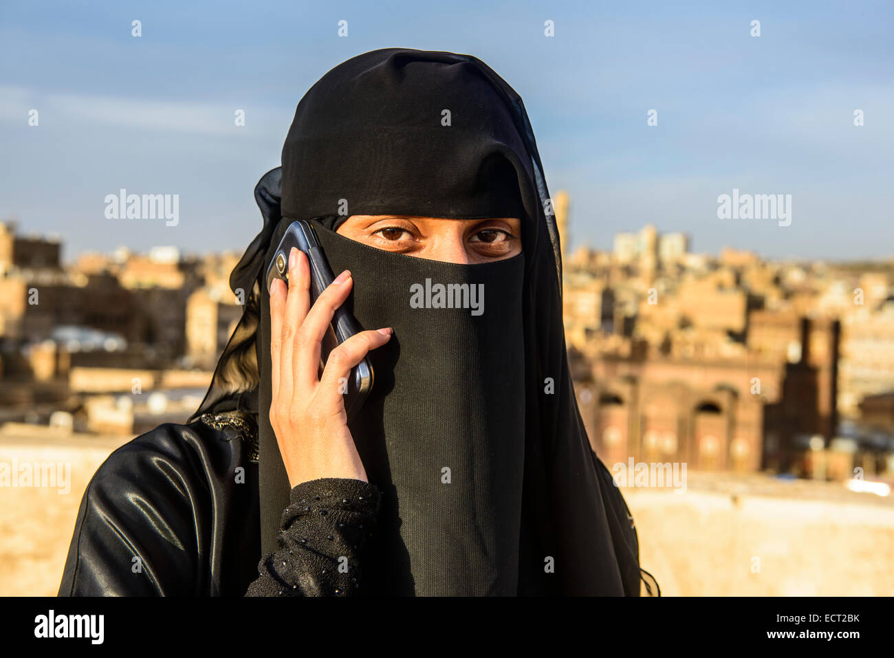 Veiled young woman on her mobile, in the old city, Sana'a, Yemen - Stock Image