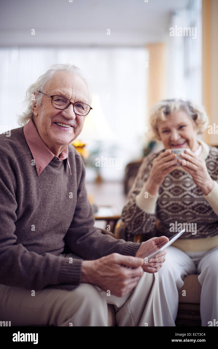Elderly man with touchpad looking at camera on background of his wife - Stock Image