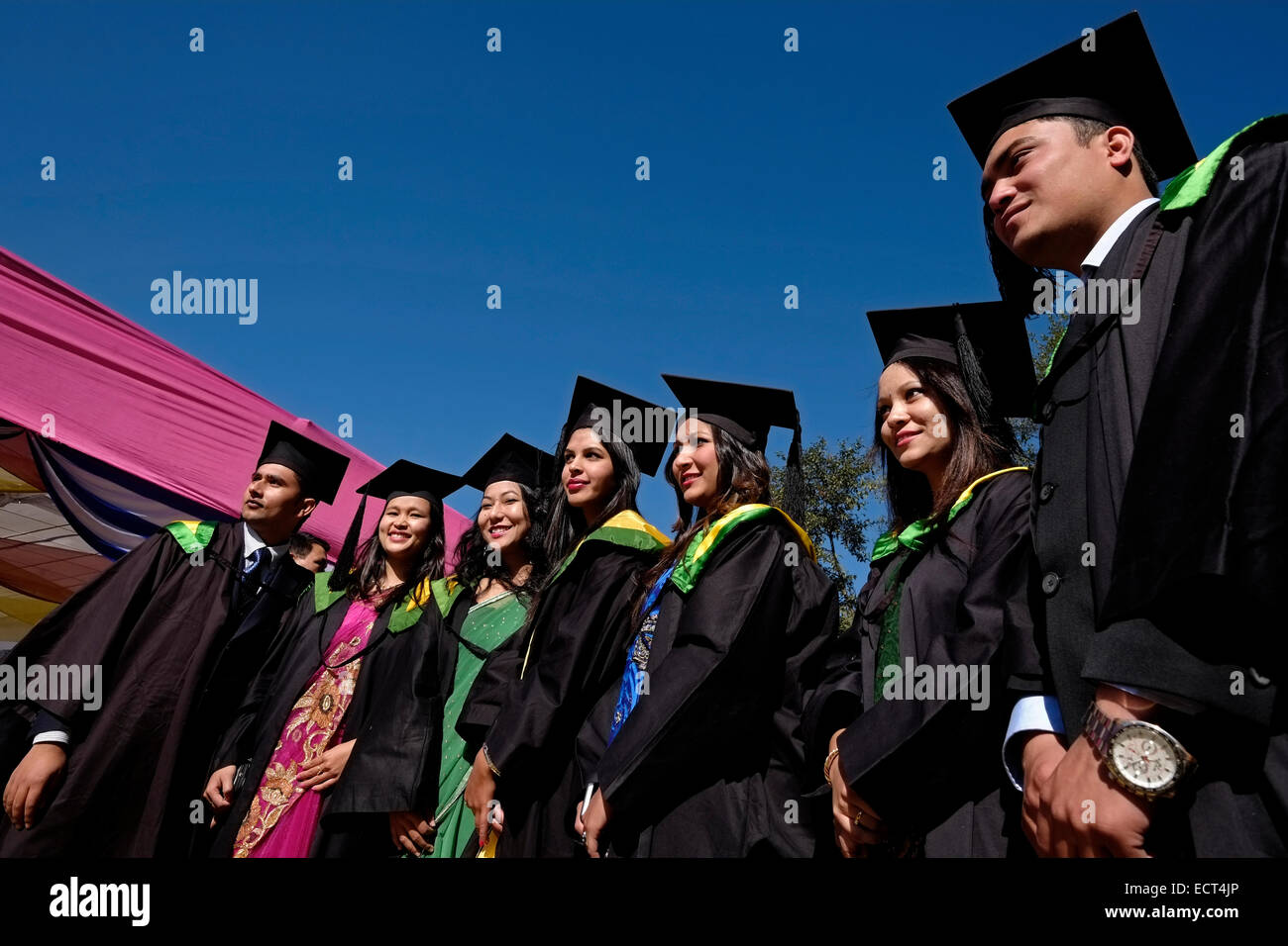 University students wearing a cap and gown posing for picture during ...
