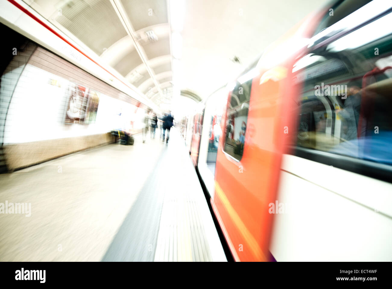 Tube train platform with moving train - Stock Image