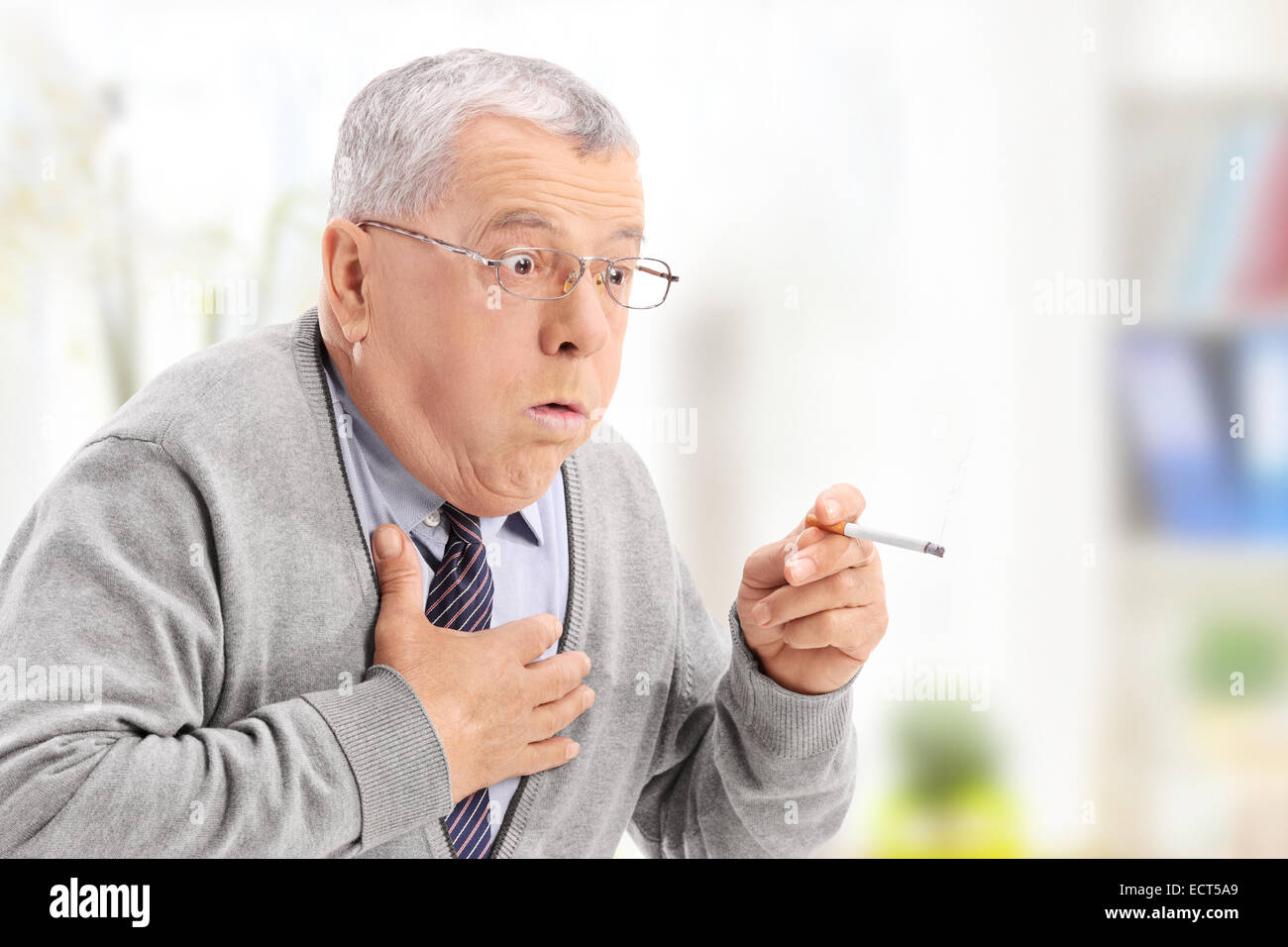 Senior man choking from the smoke of a cigarette at home - Stock Image
