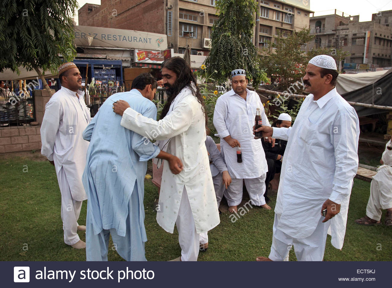 Qawwali musicians gather in the park near Data Durbar to rest and drink Coca Cola after the concert.  Pakistan, - Stock Image