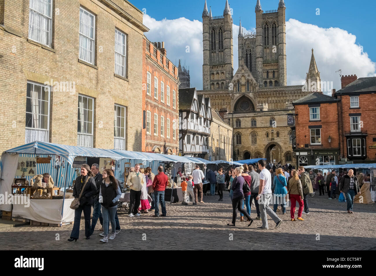 People walking round Lincoln market square, with Cathedral in background, Lincolnshire, England UK - Stock Image