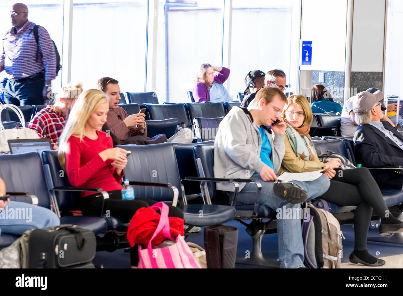 IAH, Houston Intercontinental Airport, Houston, TX, USA - passengers waiting with luggage in airport - Stock Image