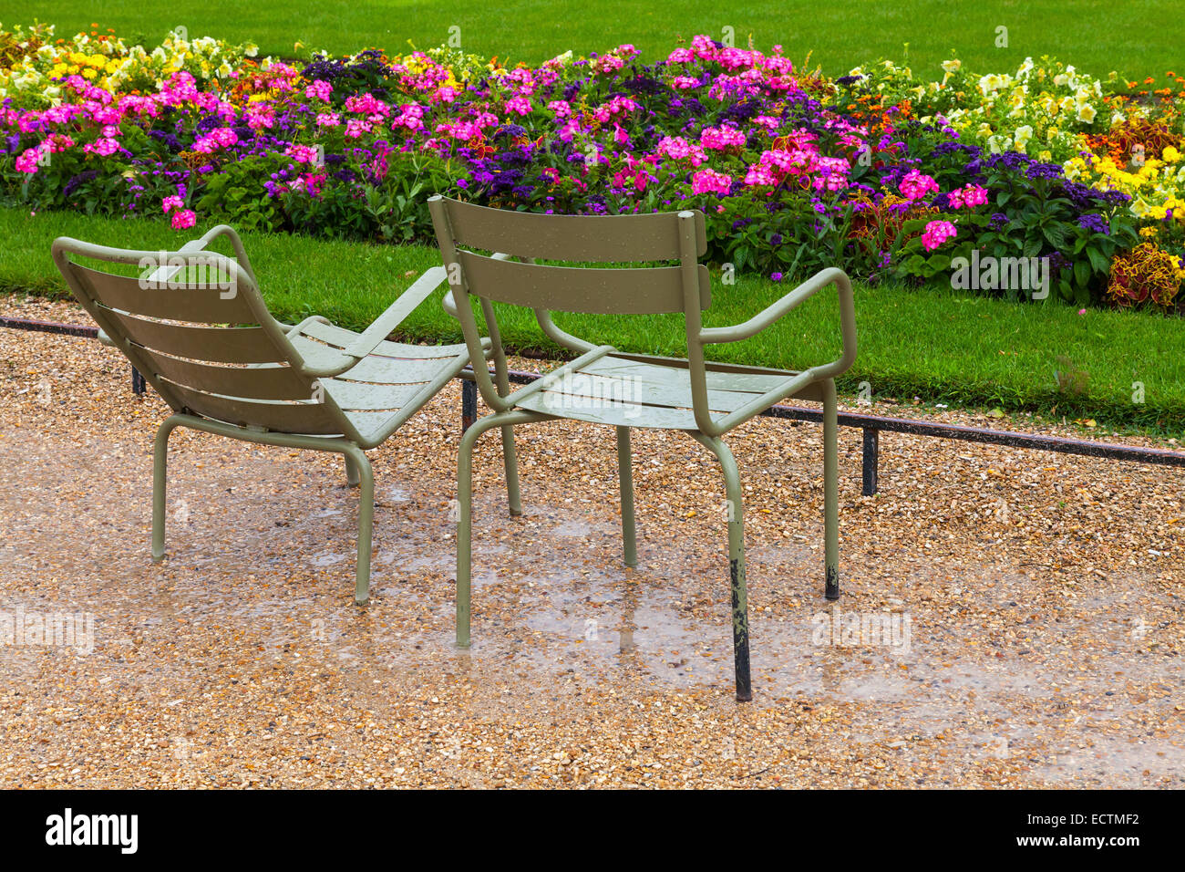 Wet Metal Armchairs In The Rainy Park With Colorful Flowers In Paris