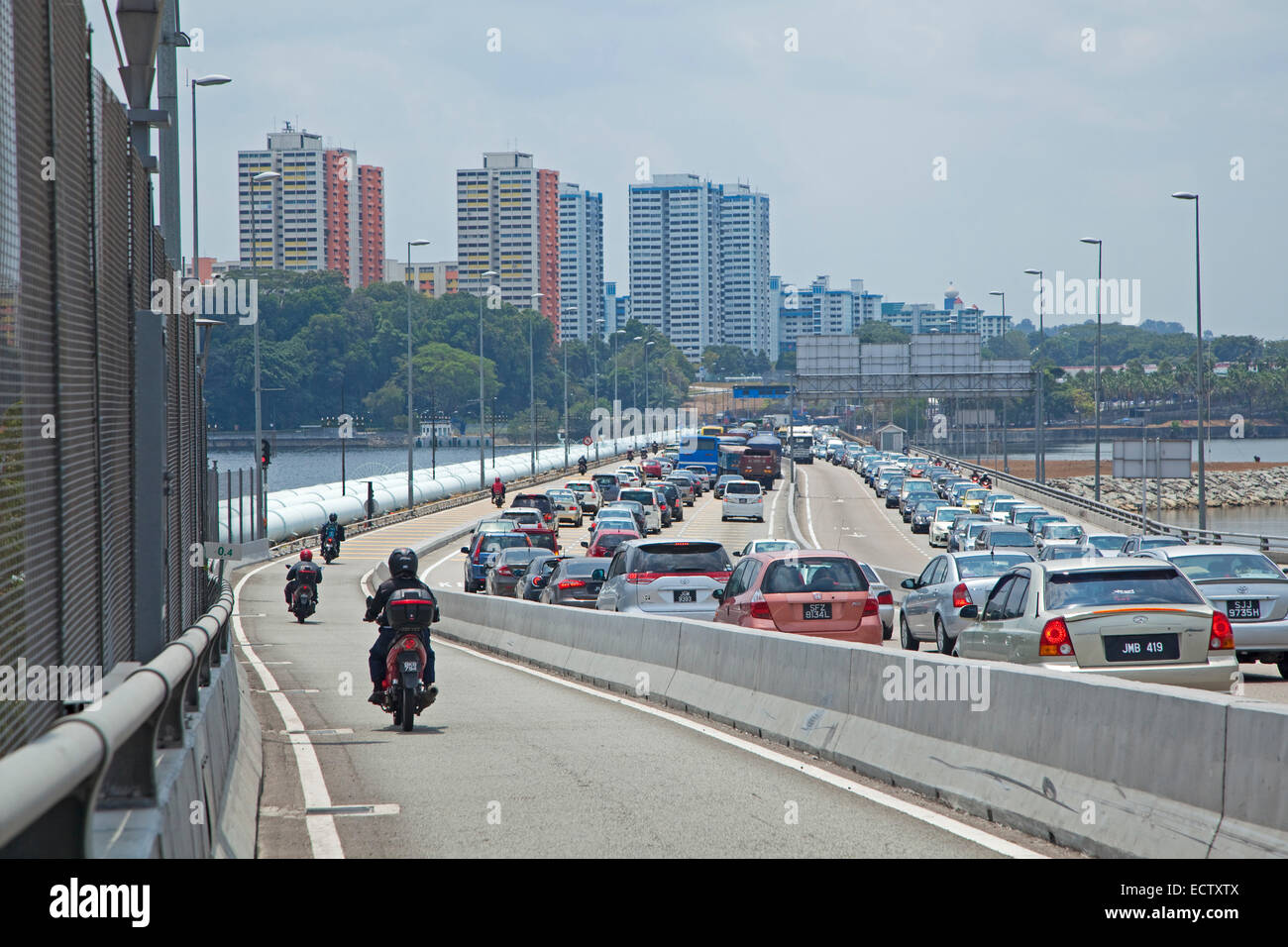 Cars in traffic jam during rush hour on the bridge from Malaysia to Singapore - Stock Image