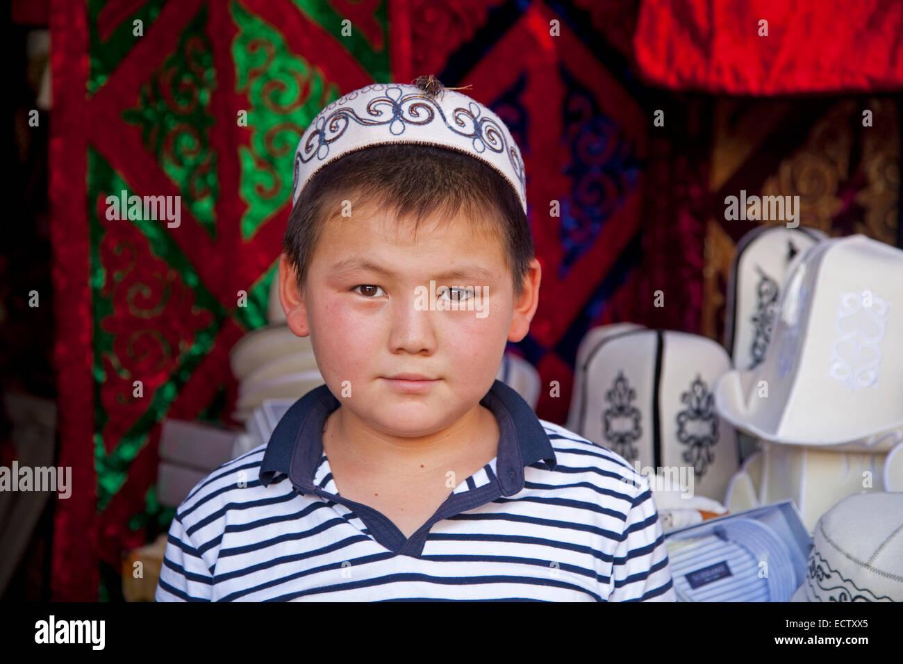Kyrgyz boy wearing traditional tubeteika at market in Osh, Kyrgyzstan - Stock Image