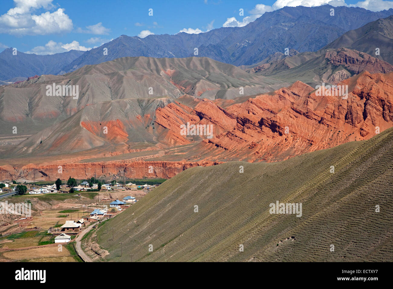 Village among colourful mountains, foothills of the Himalayas in the Osh Province, Kyrgyzstan - Stock Image