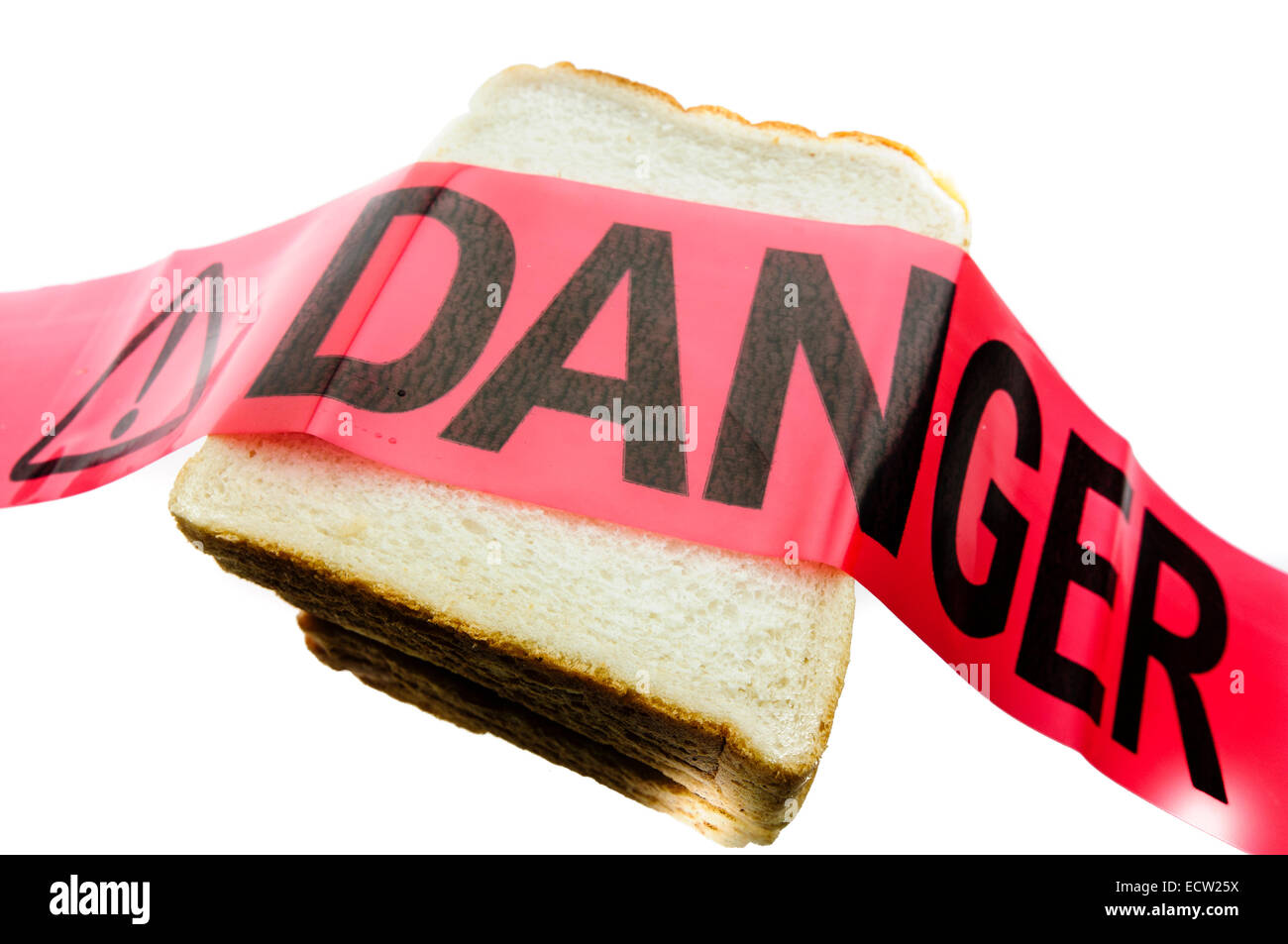 Danger tape placed over white bread, to signify the danger of gluten to people with coeliac disease - Stock Image