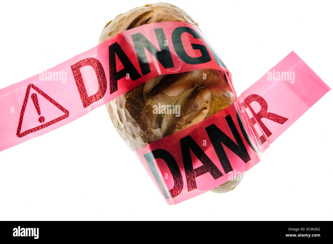 Danger tape placed over crusty bread, to signify the danger of gluten to people with coeliac disease - Stock Image