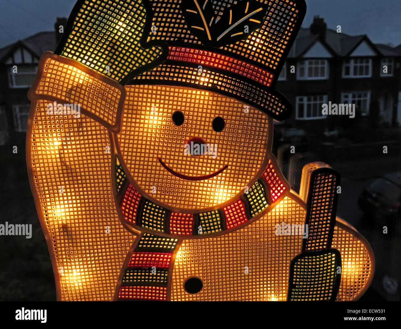 An electric snowman on a window, lit up for Christmas - Stock Image