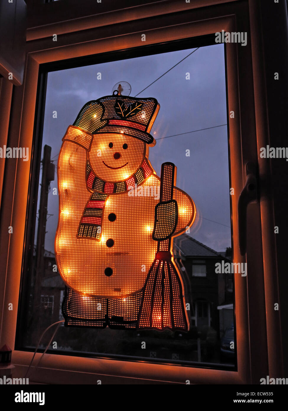 An electric snowman on a window, lit up for Christmas Stock Photo