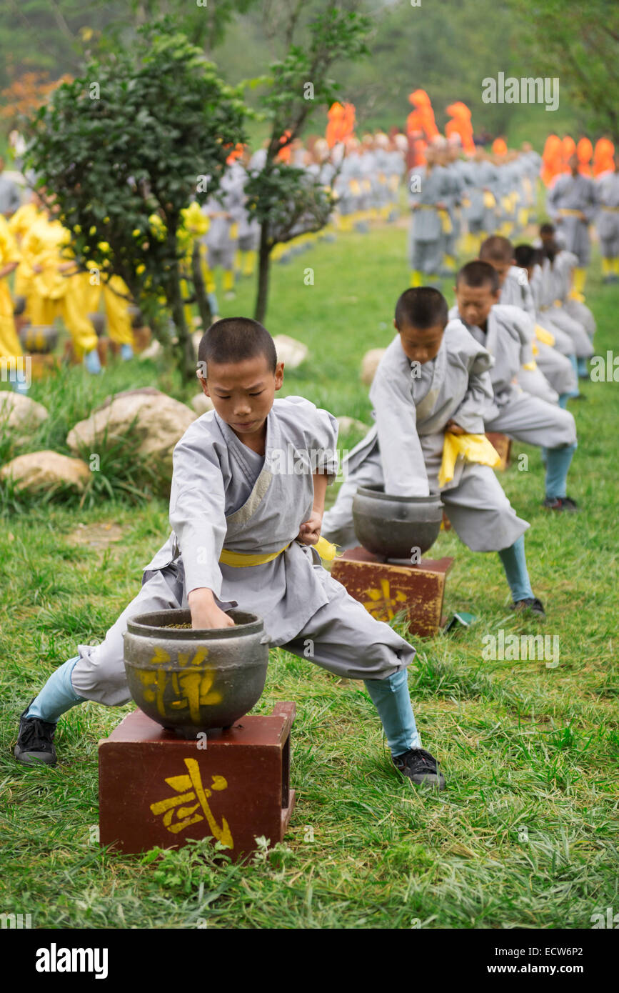 Young Shaolin Kung Fu students conditioning their fists by punching green beans in pots at the opening ceremony - Stock Image