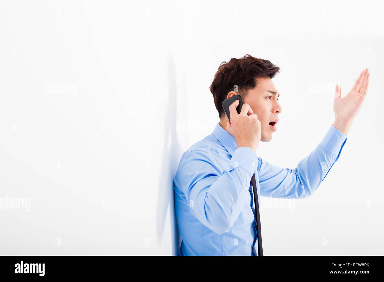angry businessman talking on the phone in office - Stock Image