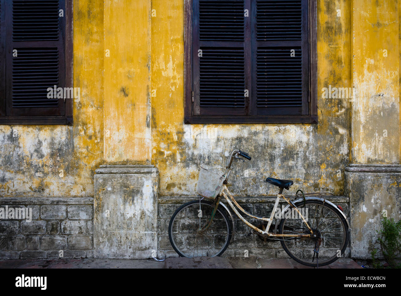 Worn bicycle leant against a delapidated wall in Hoi An Ancient Town - Stock Image