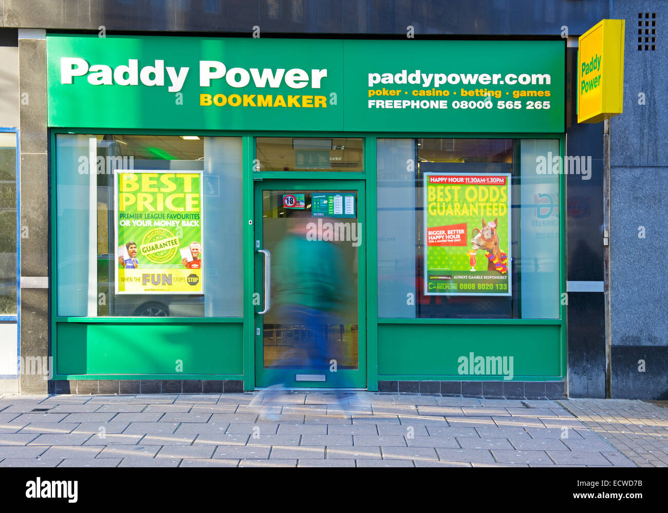 Blurred man walking past a branch of Paddy Power betting shop, England UK - Stock Image