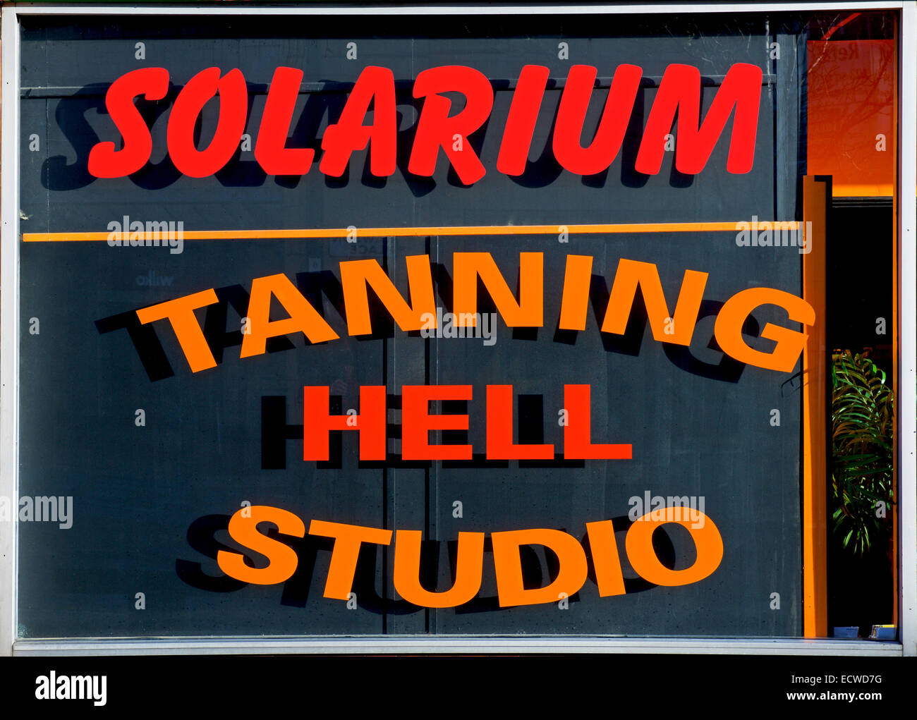 Sign for Tanning Hell Studio and Solarium, England UK - Stock Image