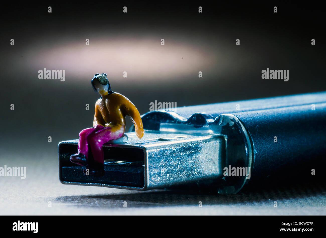 USB plug with mini figure in studio setting - Stock Image