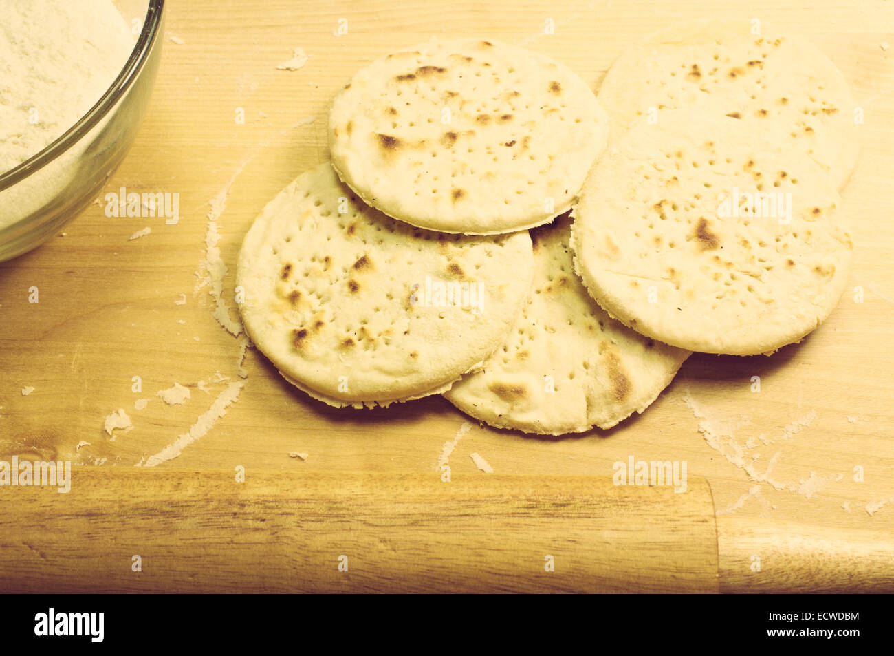 Cutting board with flour and ready matzah, pita bread, biscuits - Stock Image