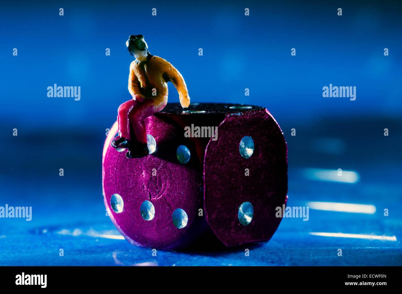 Dice with mini figure in studio setting - Stock Image