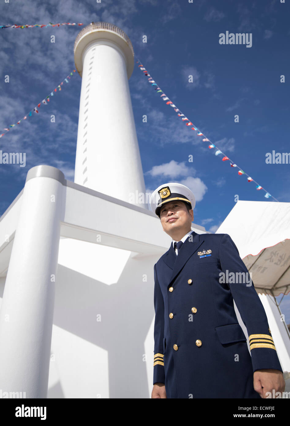 Japanese Self Defense Force coastguard officer stands in front of the Cape Zanpa Lighthouse, Yomitan, Okinawa, Japan - Stock Image