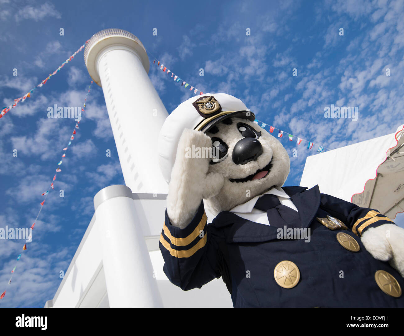 Japanese Self Defense Force coastguard mascot stands in front of the Cape Zanpa Lighthouse, Yomitan, Okinawa, Japan - Stock Image