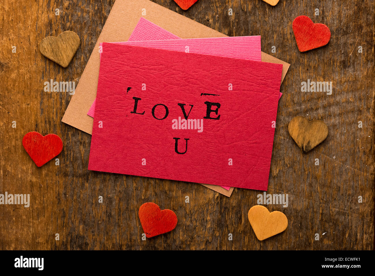 Handmade stamped valentine's day card with Love U stamped on it set on rustic wood - Stock Image