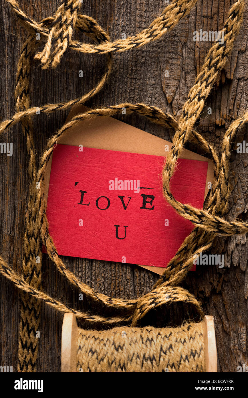 Handmade stamped valentine's day card with Love U stamped on it set on rustic wood wrapped with twine - Stock Image