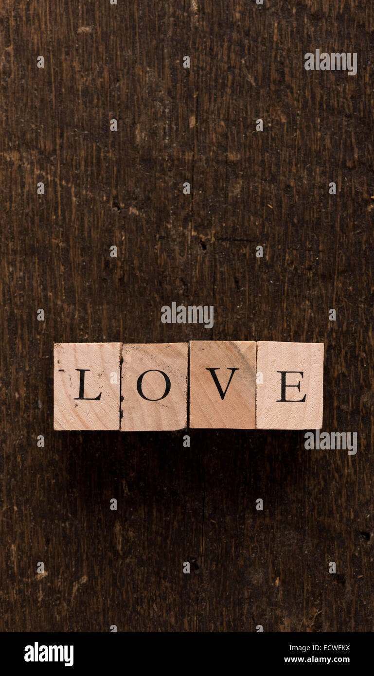 Stamping blocks with the word LOVE spelled out set on rustic wood Stock Photo