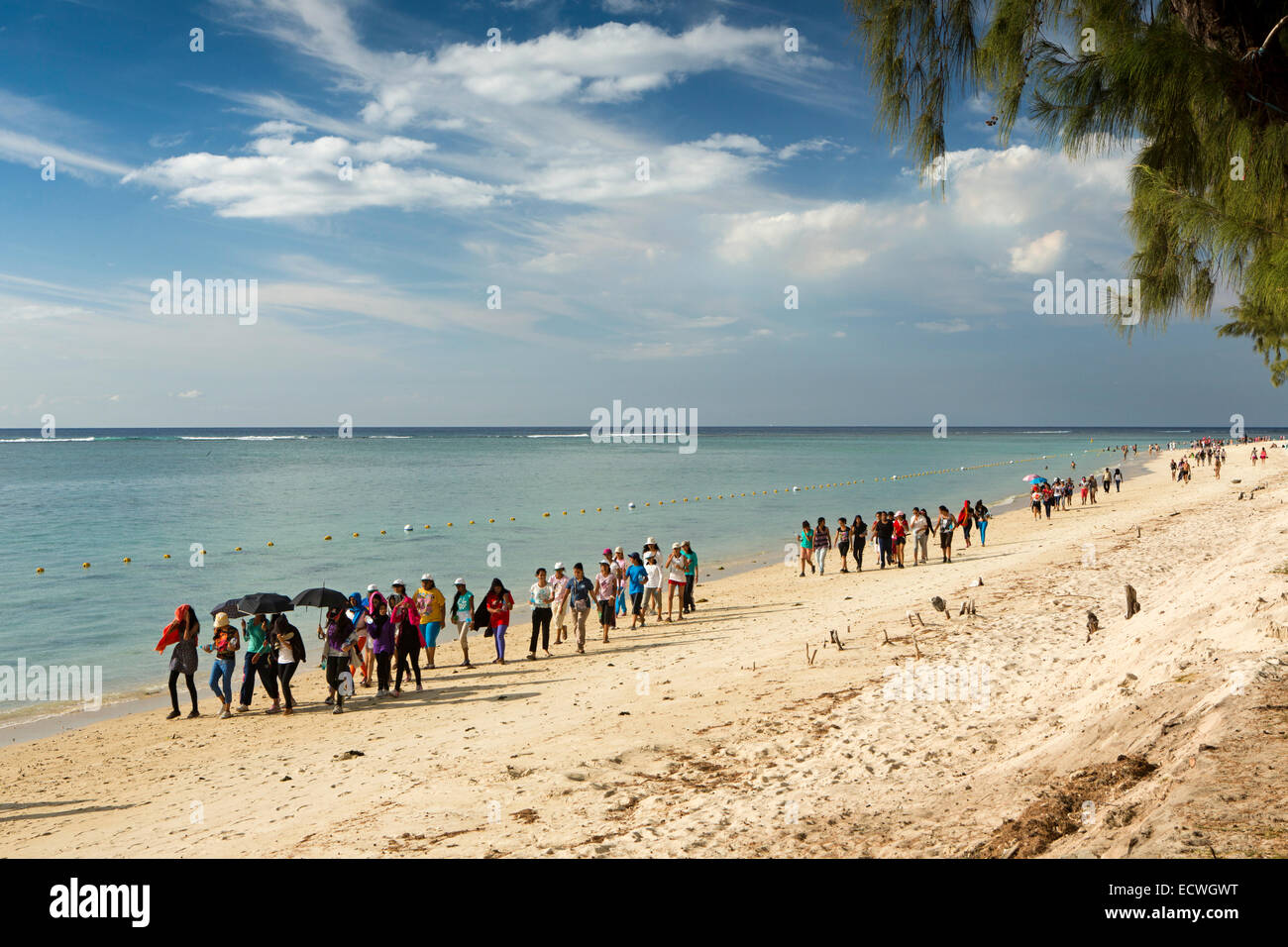 Mauritius, Flic en Flac, Public Beach, crowds of young people walking along beach at weekend - Stock Image