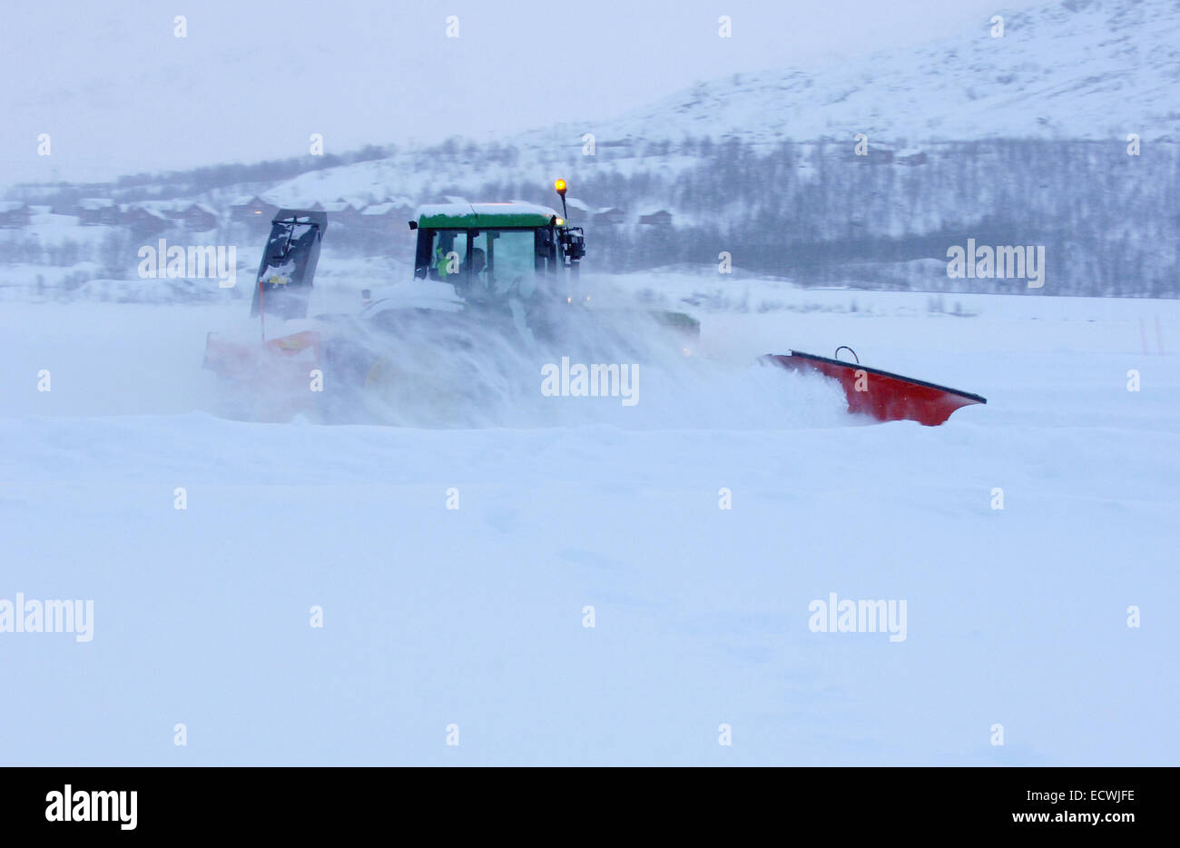 Snow plough tractor driving on snow and ice clearing a road near the arctic circle in Sweden. Volvo XC70 using winter - Stock Image