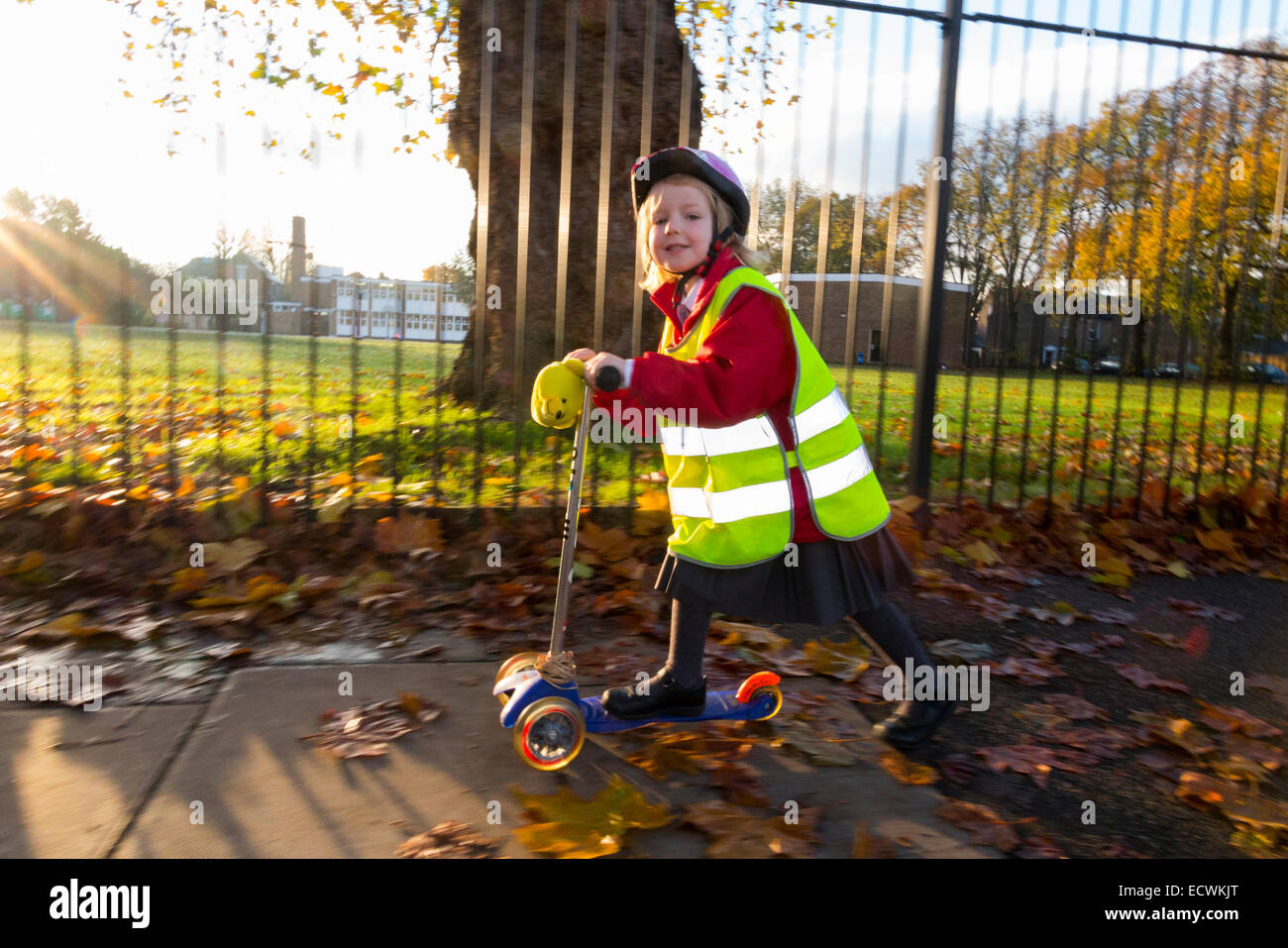 Child / girl on scooter in hi vis / high visibility vest jacket scootering / going to Reception class on a scooter - Stock Image