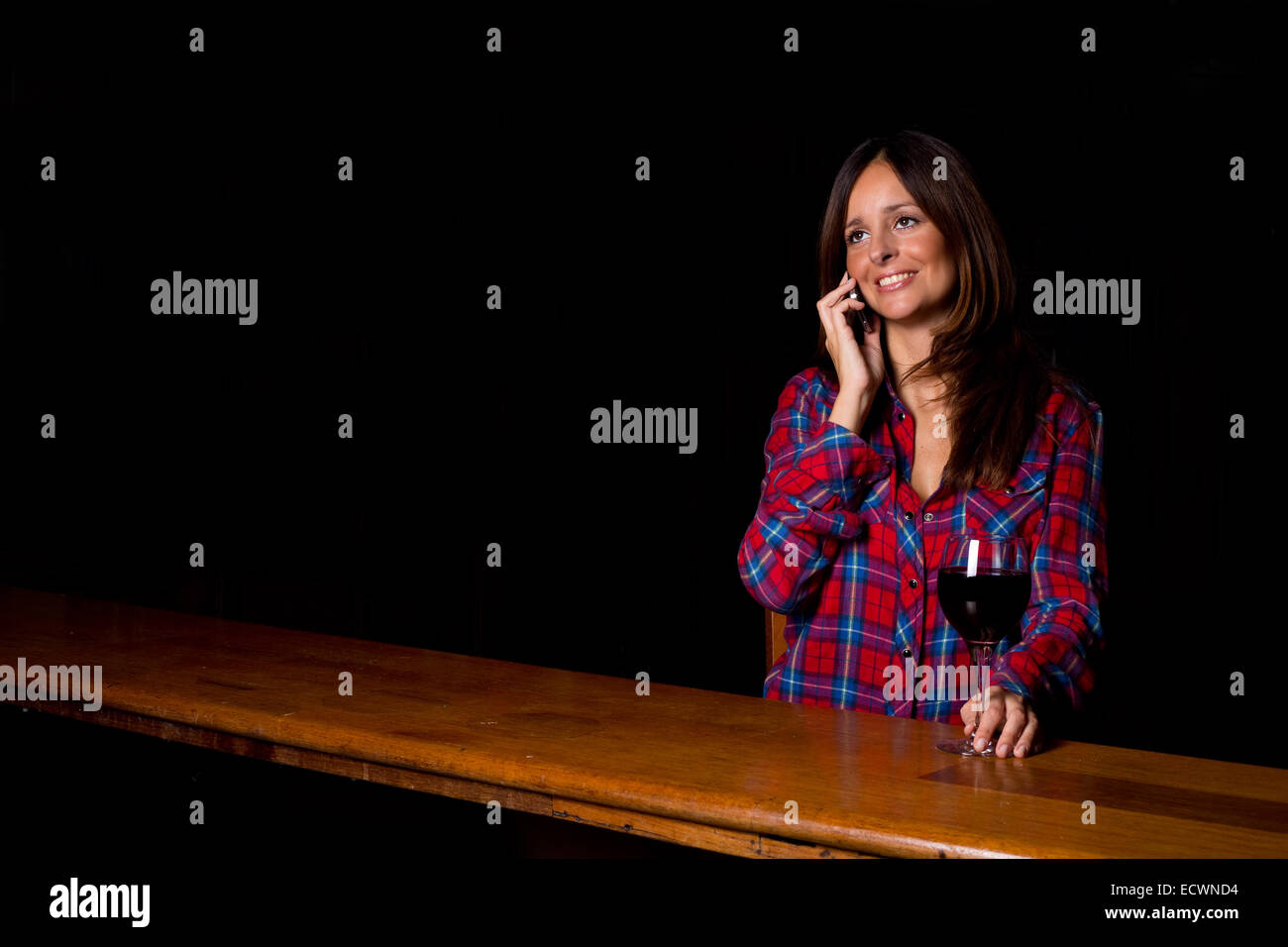 young woman making a phone call at the bar - Stock Image